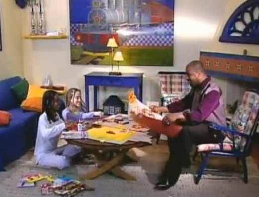 Duas meninas sentadas no chão de uma sala bem decorada recortando cartazes e uma homem negro sentado no sofá
