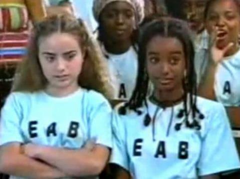 Duas meninas, uma negra e outra branca vestido o mesmo uniforme escolar, elas estão sentadas