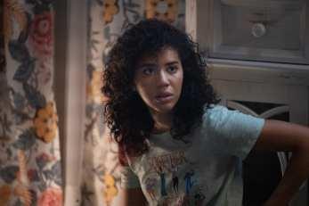 Mulher preta sentada, com expressão assustada, dentro de um quarto com cortina colorida ao fundo