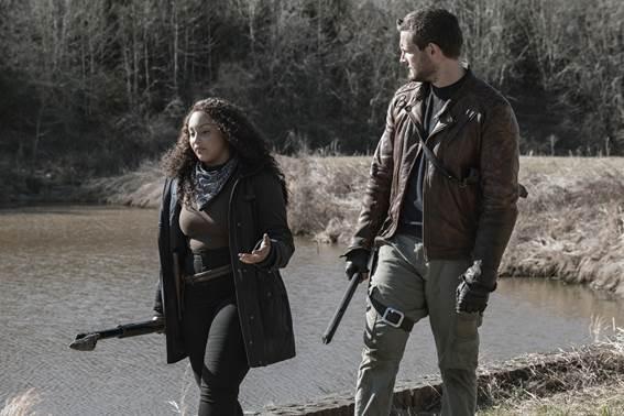 Duas pessoas vestidas de preto com armas andando próximas a um rio