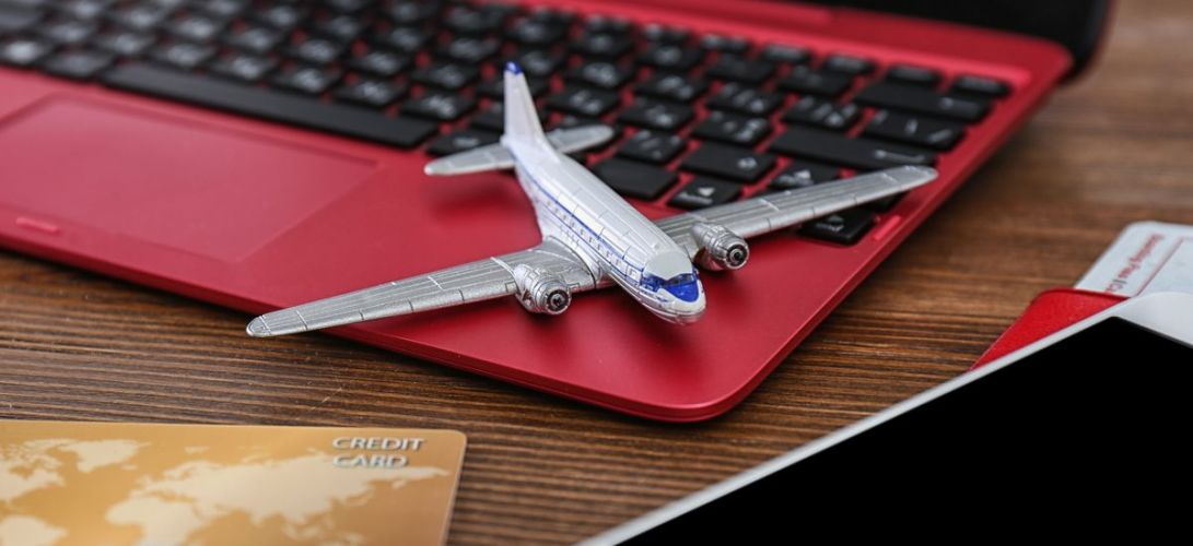 Composition with airplane model and laptop on wooden table. Travel agency concept