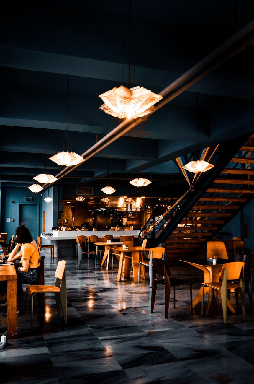 trendy interior of cafe with creative lamps and wooden furniture