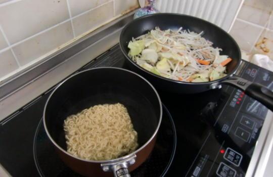 袋メンを茹でながら野菜を炒めている画像