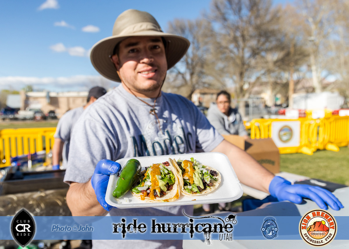 Smiling man in a hat, holding out a plate of tacos with a grilled jalapeno.