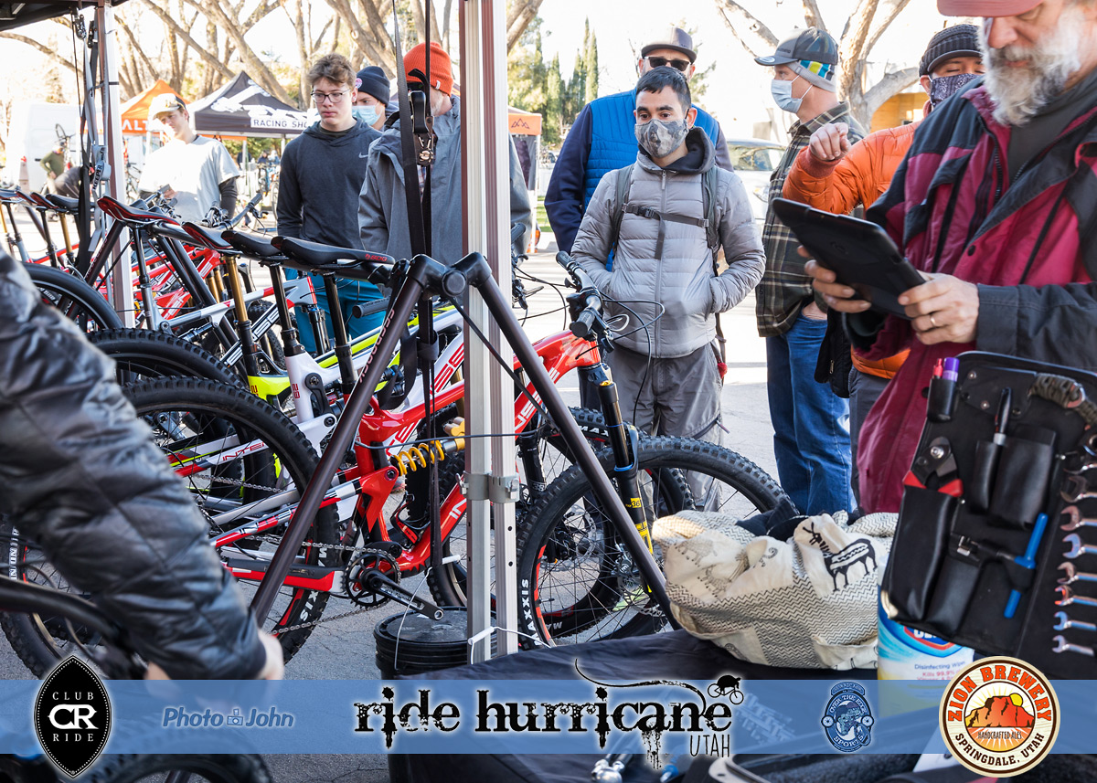 Mountain bikers waiting for demo bikes at a festival booth.