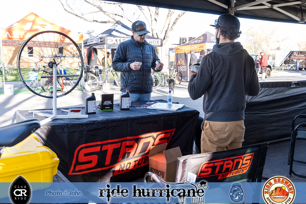 Two men talking at a bicycle festival vendor booth