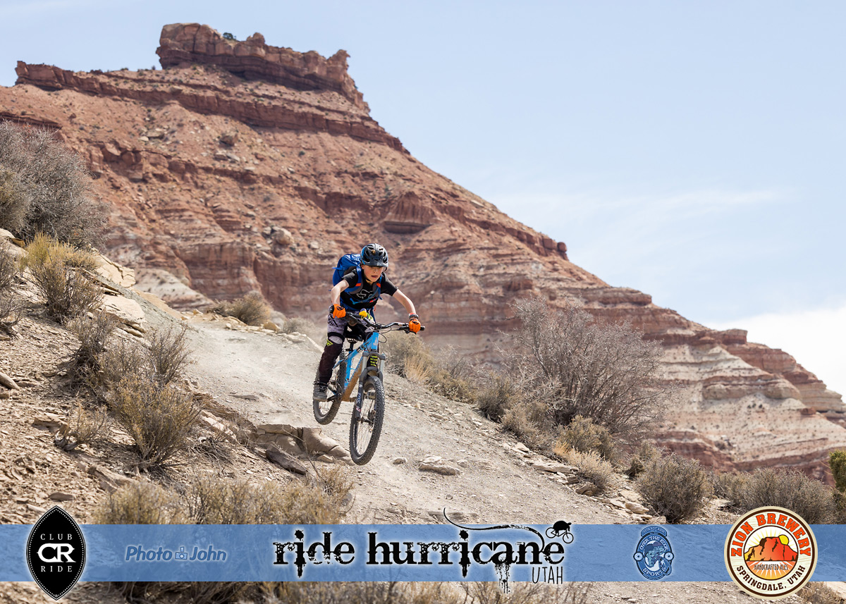 Boy on a mountain bike in the air on a steep trail with Southwestern background.