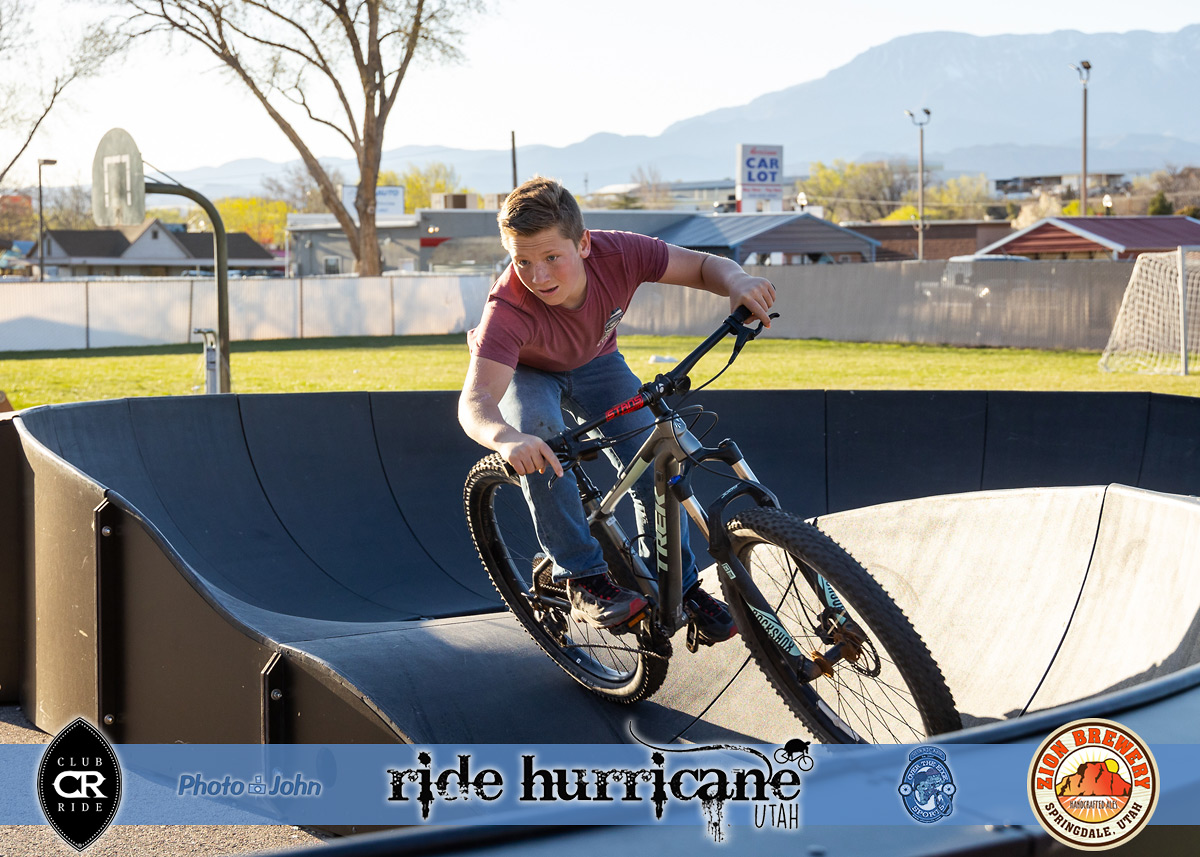 A kid on a mountain bike, looking through a corner while riding a pumptrack.