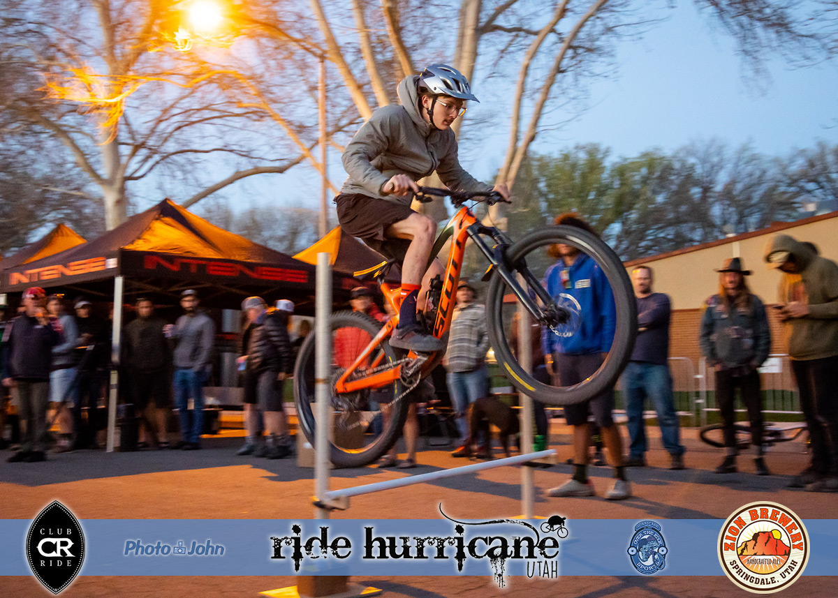 Bicyclist hopping over a high jump bar at a festival.