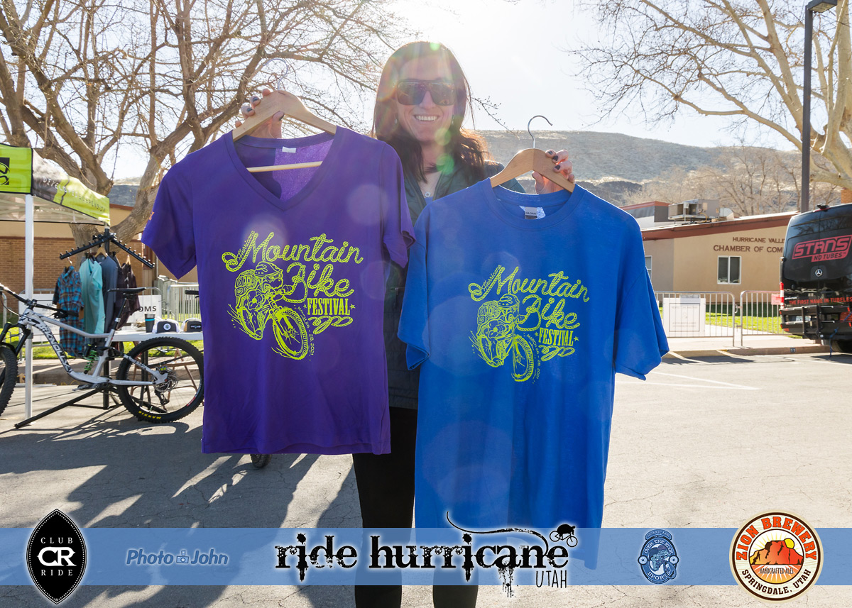 Smiling woman in sunglasses holding mountain bike festival T-shirts.