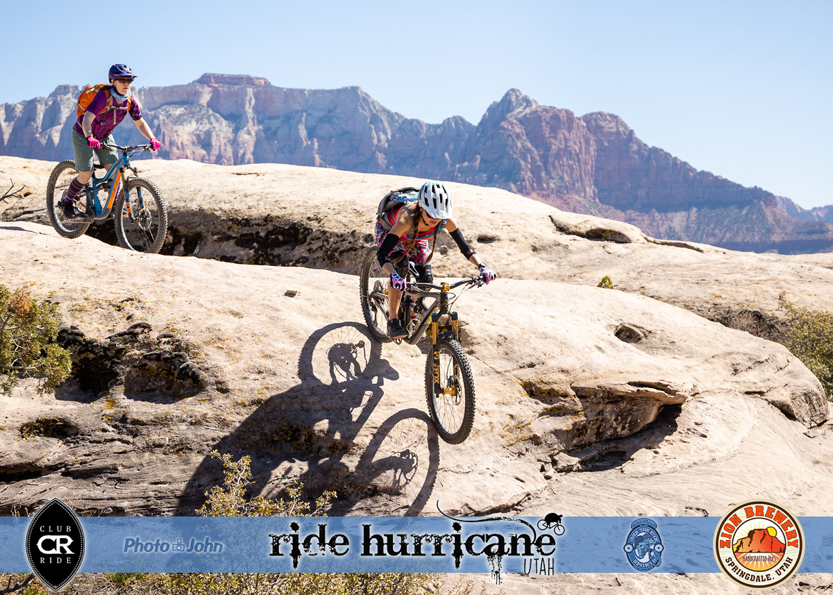 Two women mountain bikers riding sandstone rocks with Zion National Park cliffs in the background.