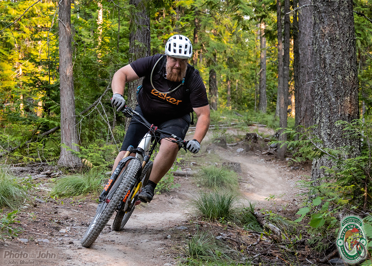 A tight photo of Tim Krueger of Esker Cycles, riding his Esker mountain bike on a twisty forest trail.