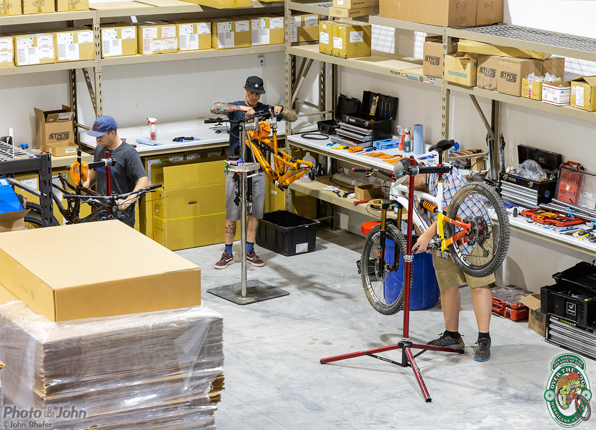 Looking down from above on three men building mountain bikes in the Esker Cycles warehouse.