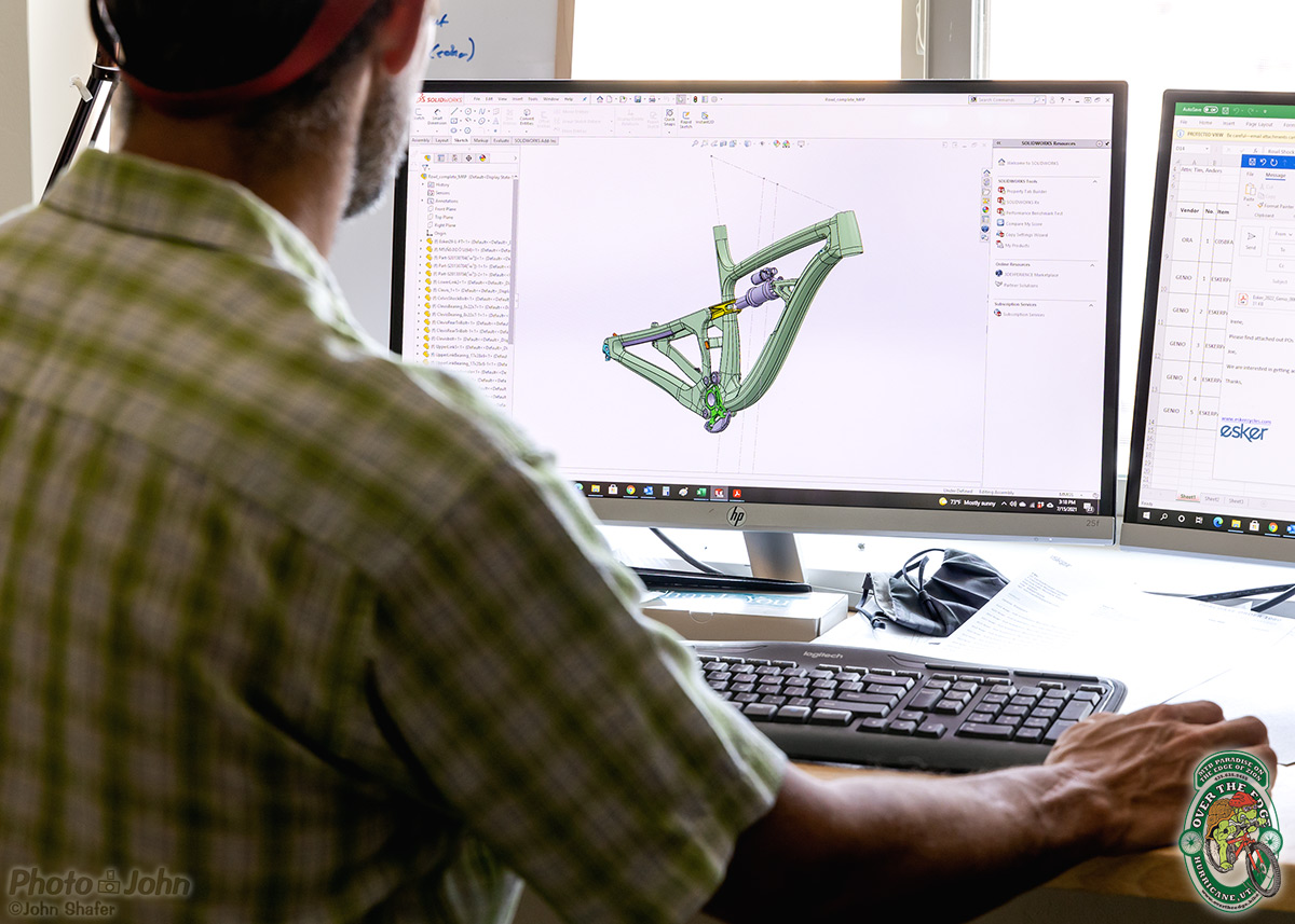 Looking over a shadowy person's shoulder at a mountain bike frame design on a computer monitor.