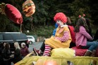 A sad kid in a Ronald McDonald costume on a parade float.