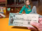 """A parent holds a U.S. Treasury check for $300 addressed to """"Every parent."""""""