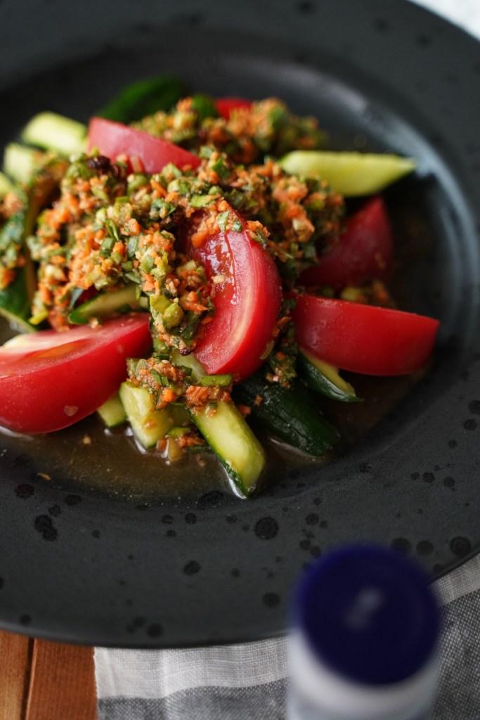 黒いお皿に盛られたスタミナ満点!トマトときゅうりのニラだれサラダ