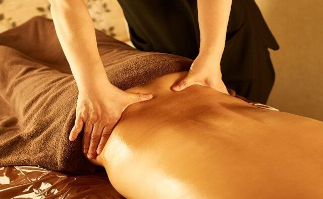 薄暗いメンズエステサロンで腰の施術を受ける男性