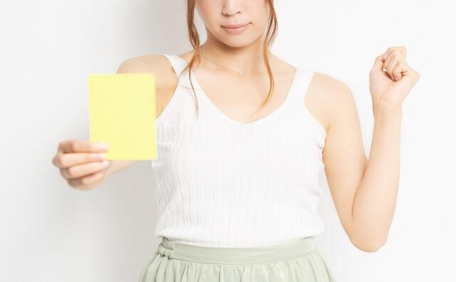 イエローカードを手に持つ若い女性のイメージ