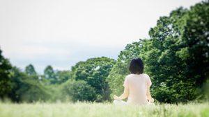 自然に囲まれた場所で深呼吸している女性の画像