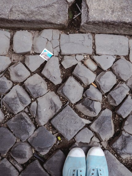 A broken street with a discarded sugar wrapper.