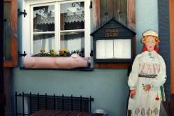 Zachęcające prosiaczkowe skrzynki i drewniana pani przed restauracją na Starym Mieście