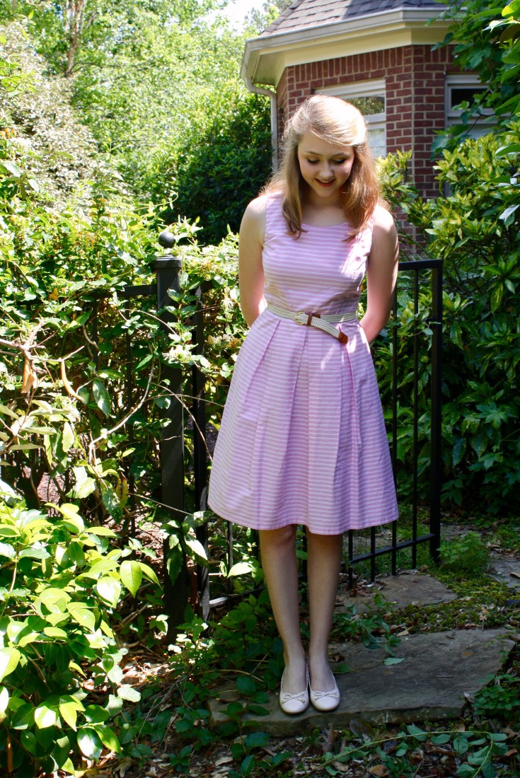 Bonnie stands in the garden with her hands behind her back, looking at the sound. She wears a pink and white striped summer midi dress, a woven belt, and blush pink colored block heel pumps.