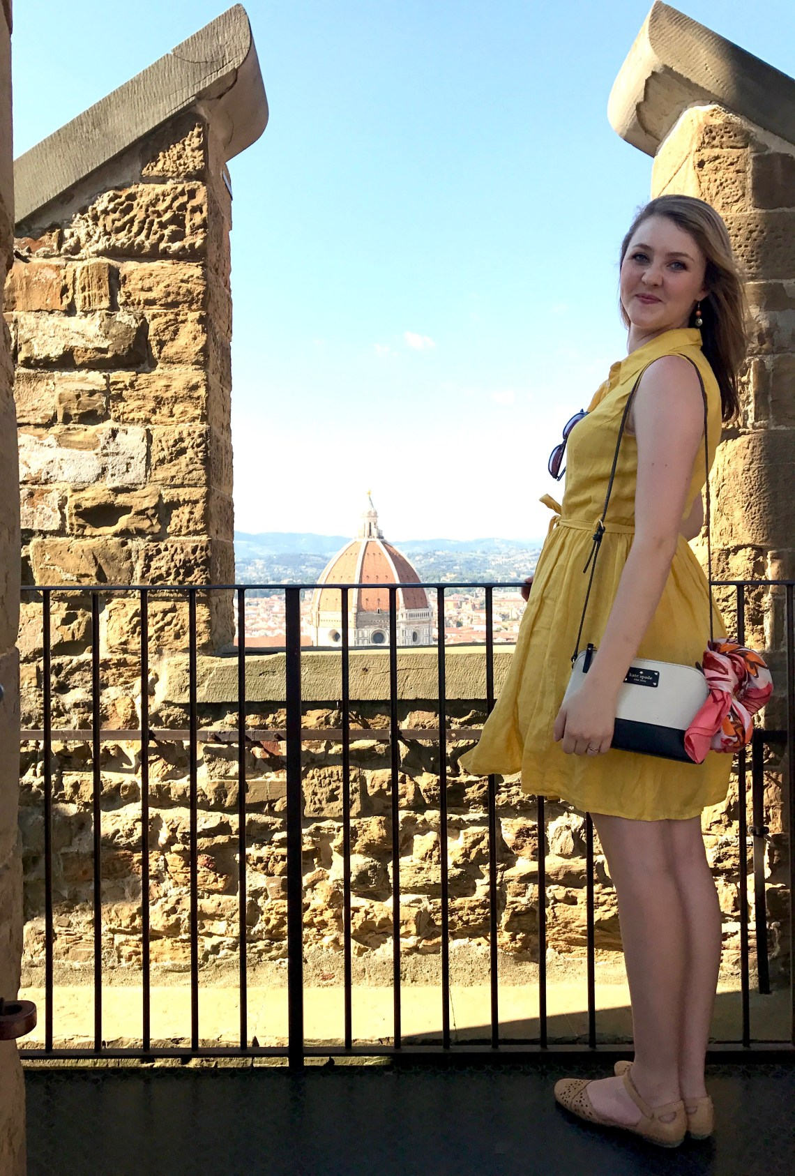 yellow shirt dress standing in front of the Duomo with Kate Spade purse and pink scarf