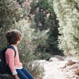 child carrying backpack sitting on a rock