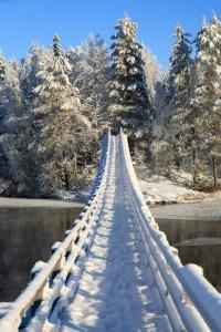 Luminen riippusilta Oulujoen yli. Vastarannalla luminen metsä ja sininen taivas.