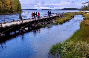 Ihmisiä joen luusuassa kalastuslaiturilla