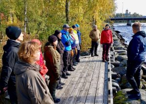 Ihmisjoukko joen rannalla puisella laiturilla