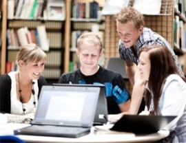 Group of smiling young adults around a laptop in a library