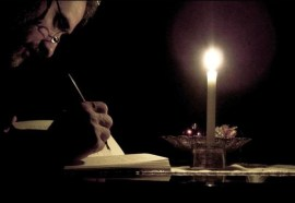 Man writing by candlelight