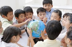 Group of oriental children crowding around a model globe