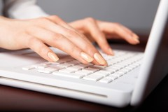 Woman's hands typing on a white laptop