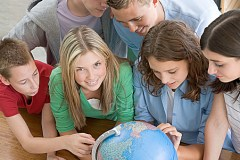 Group of children gathered around a globe