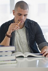 Young man chewing pencil while studying