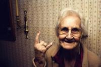 Elderly lady making a devil gesture with her hand