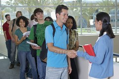 Students shaking hands with their teacher