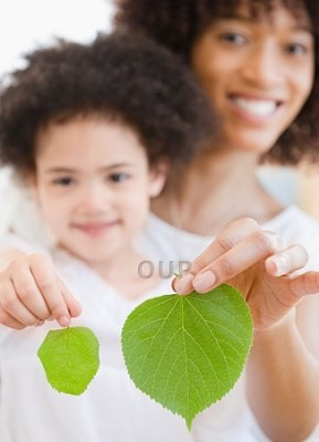 Mother and daughter holding leaves