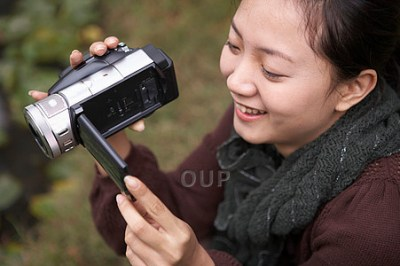 Asian woman using video camera