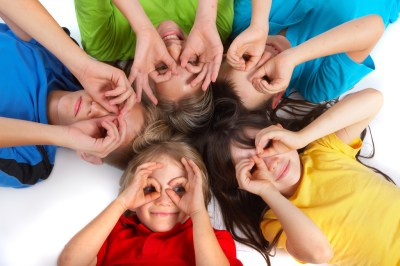 Kids lying in a circle making goggle eyes