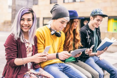 teenagers reading on books, phones and tablets