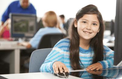 Girl sat at computer smiling