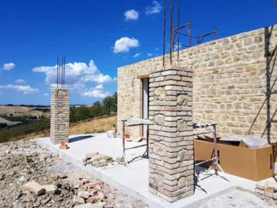 Finished Portico Columns behind a new stone house in Le Marche, Italy