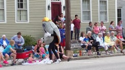 Person in clam costume greets paradegoers