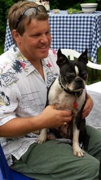 Man holding graying Boston terrier