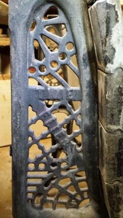 "Detail of wrought-iron school desk leg, saying ""Time flies."""