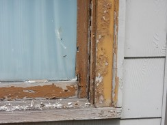 Window trim with peeling brown paint